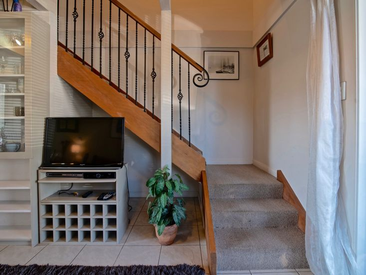 TV and stairs to 2nd level