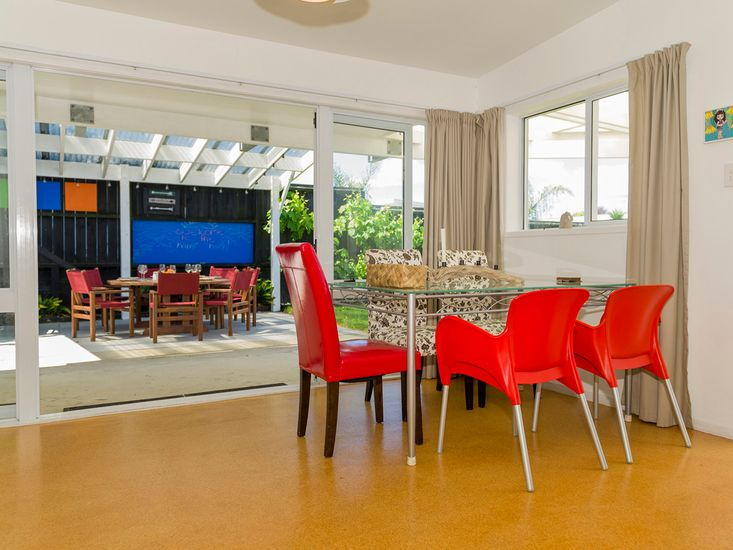 Dining table flows out on the sheltered outdoor BBQ and dining area