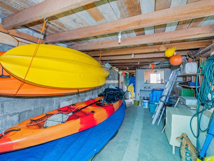 Kayaks and boogie boards under the house